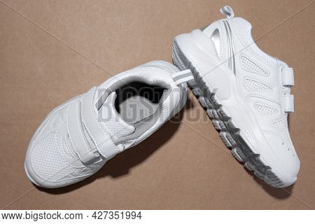 Top View White Unisex Running Shoes With Velcro Fasteners For Easy Footwear With Hard Shadows Isolat
