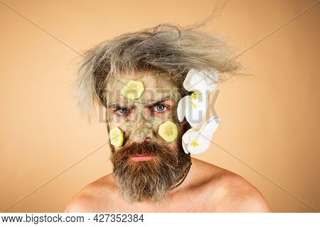 Funny Man With Clay Mask And Cucumber Slices On Face. Male Spa, Dermatology, Wellness And Facial Tre