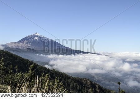 Teide Volcano Peak With Snow In Clear Day With A White Clouds In The Foreground