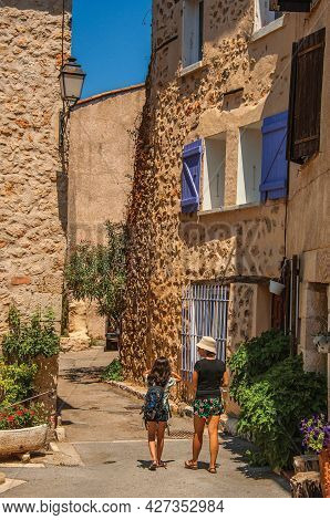 Chateaudouble, France - July 11, 2016. Woman And Child Walking An Alley With Building And Flowers In