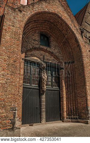 Old Wooden Gateway In Gothic Church On A Sunny Day, In An Alley Of Bruges. A Graceful Town That Is A