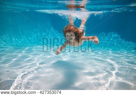 Kid Swimming Underwater And Smiling. Happy Kid Swims In Pool Underwater, Active Kid Swimming Under W
