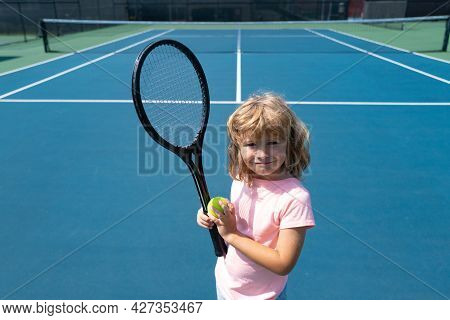 Funny Kid Tennis Player On Tennis Court. Child Boy With Tennis Racket And Tennis Balls.