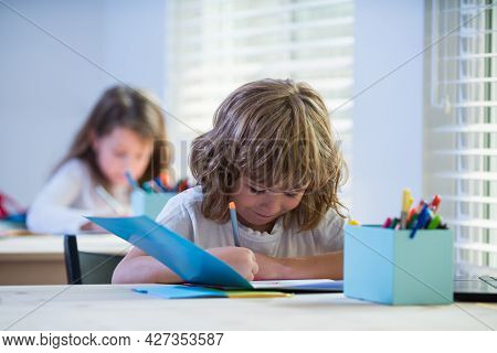 Cute Boy Drawing In Classroom. School Kid Writing In Copybook And Sitting At Table In Classroom.