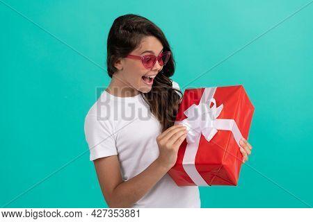 Fashionable Amazed Teen Girl In Sunglasses Open Gift Box, Amazement