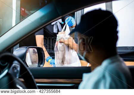 Selective Focus To Hand Of Staff Wearing Medical Glove And Mask  To Handed A Food To Customer. Drive