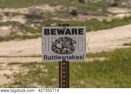 Badlands National Park, Sd, Usa - June 1, 2008: Black On White Beware Of Rattlesnakes Sign With Fade