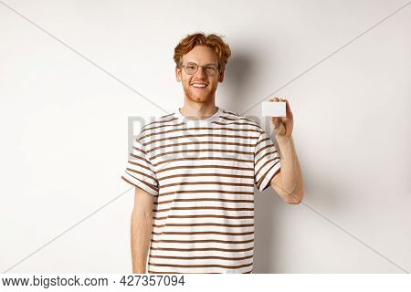 Shopping And Finance Concept. Smiling Young Man With Bristle And Red Hair Showing Plastic Credit Car