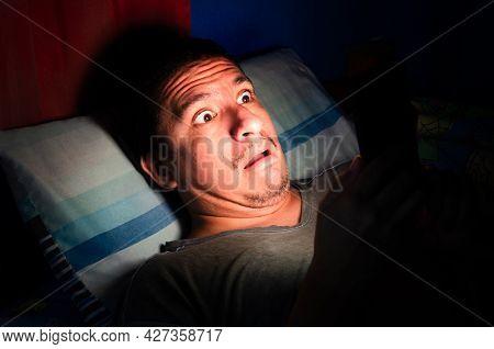 Anxious And Awake Man Looks At His Phone At Night In The Dark.