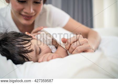 Asian Loving Beautiful Mother Take Care Asleep Young Comfortable Kid. Caring Parent Mom Put Blanket