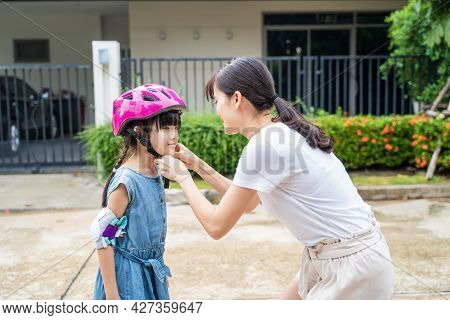 Asian Mom Put On Sport Helmet To Little Kid For Safety Before Exercise. Beautiful Loving Mother Wear
