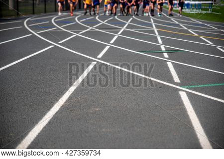 Runners Take Off At Starting Line. Selective Focus On Foreground Track With Copy Space, Runners Moti