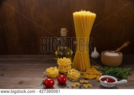 Pasta and food ingredient on wooden table background. Raw pasta assortment of italian food at tabletop