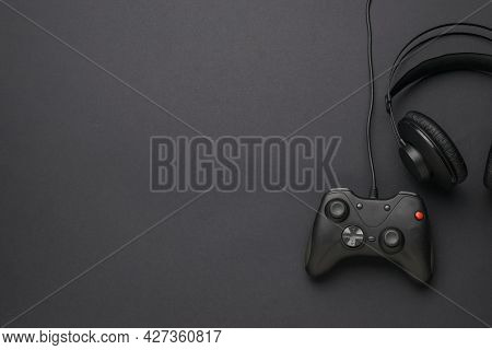 Headphones And A Game Console On A Black Background. A Device For Playing Computer Games. Flat Lay.