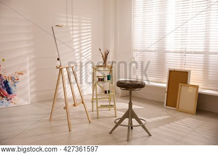 Wooden Easel With Empty Canvas And Stool In Art Studio