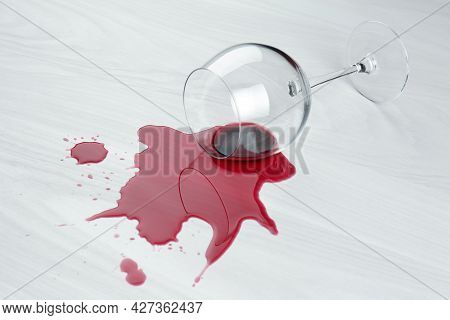Overturned Glass And Spilled Wine On White Wooden Table