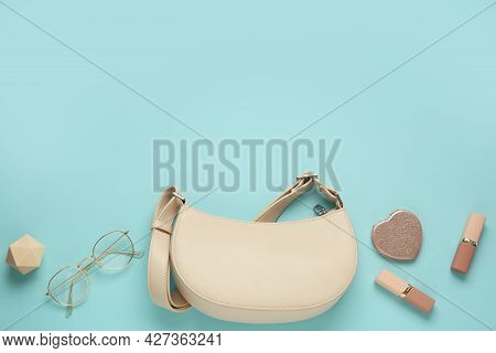 Flat Lay Composition With Stylish Baguette Handbag On Light Blue Background. Space For Text
