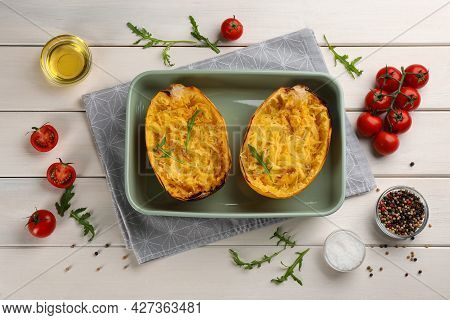 Halves Of Cooked Spaghetti Squash In Baking Dish And Ingredients On White Wooden Table, Flat Lay