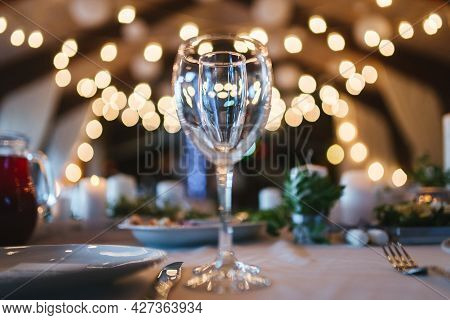 Two Glasses For Wine And Champagne Are On Table On White Tablecloth Against Background Of Blurred Wa