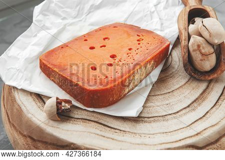 Large Piece Of Cheddar Cheese With Macadamia Nuts On A Wooden Board. A Rectangular Piece Of Fat Oran