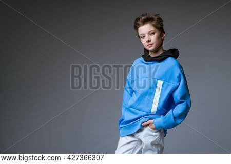 Portrait Of A Cute Guy Of European Appearance Smile In A Blue Sweatshirt Posing On A Gray Background
