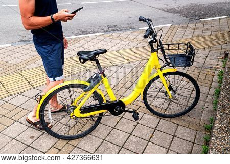 Bike Yellow And Mobile Phone. Man Using E Vehicle Rent Service With Smartphone In Urban City Street