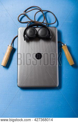 Laptop And Skipping Rope On A Blue Background. The Image Of A Sports Man. Vertical Frame.