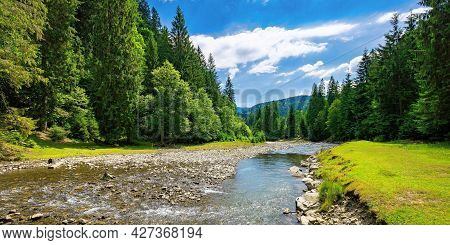 Summer Landscape With Mountain River. Water Flows Down The Valley Among Grassy Shore With Stones And