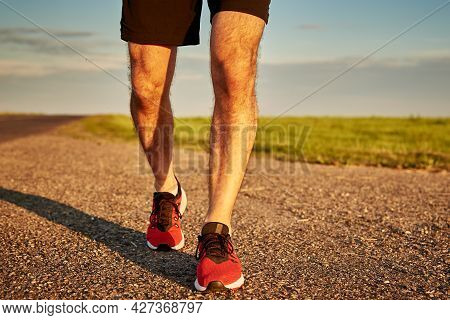 Male Runner Feet On Road At Sunset, Close Up. Sport Sneakers For Jogging. Fitness And Healthy Lifest
