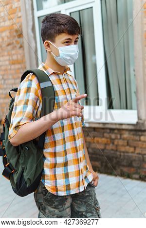 teen schoolboy on the way to the school, they use protective face masks to protect against virus, coronavirus infection, education and back to school concept