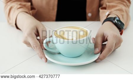 Coffee Latte Art ,laptop On The Table.hand With Coffee Cup Latte Art