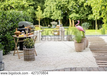 Beautiful Backyard In Natural Boho Style With Garden Furniture, Greens And Pink Flamingo