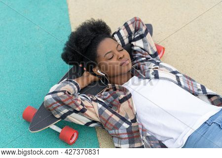 Carefree Afro Girl Young Adult Chill Lying On Longboard Listen Music Wear Wireless Earphones With Cl