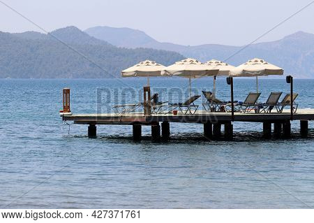 Beach Holiday On Sea Resort, Pier With Lounge Chairs And Parasols. Scenic View To The Green Mountain