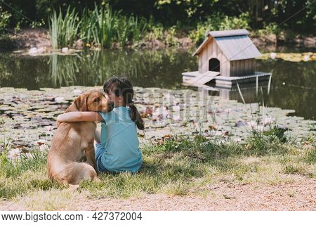 Friendship Of Animals And Children, People. Caucasian Girl Sits On The Bank Of A Pond, River And Hug