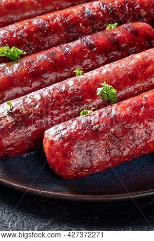 Grilled Sausages Close-up On A Plate On A Dark Background. Frankfurter Bratwurst, Beef And Pork Saus