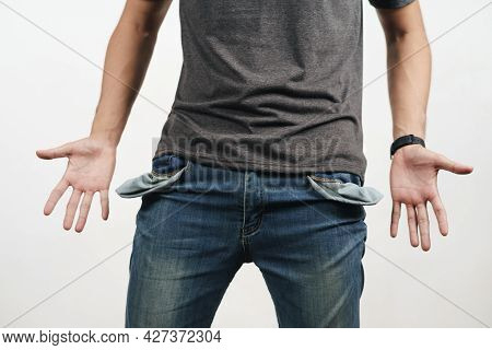 Man Turning Out The Jean Pocket To Showing Empty Pocket. Bankrupt, Bad Economy, No Money Concept.