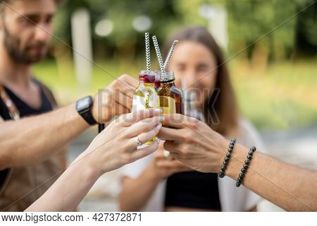 People Clinking Bottles With A Strong Alcohol Drinks On A Picnic Outdoors, Close-up. Holding Bottles