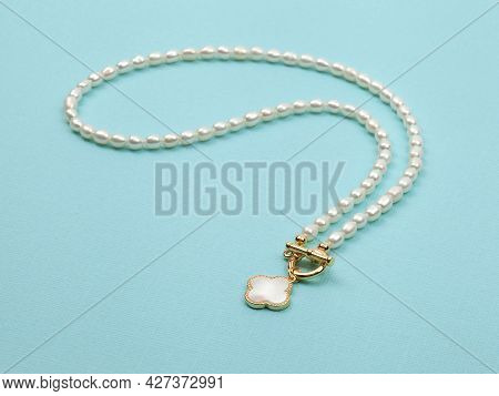 Luxury Elegant Baroque Pearl Necklace With Pendant On Bright Turquoise Textured Background.  Close-u