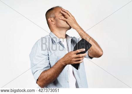 Upset Mature Man Holding His Empty Wallet On White Background. Financial Crisis, Bankruptcy, No Mone