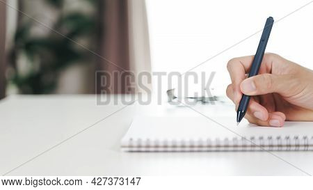 Close Up Of Young Man In Casual Cloth Hands Writing Down On The Notepad, Notebook Using Ballpoint Pe