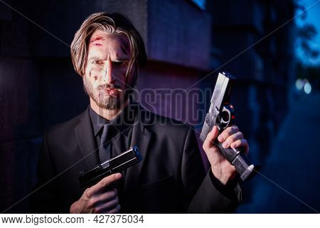 Underworld, action movie. A wounded special agent armed with guns looking at camera. Mafia Wars.
