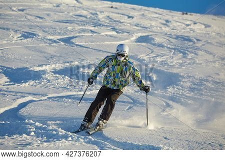 LES ORRES, FRANCE - JANUARY 23, 2015: Young skier coming down fast in fresh powder snow off-piste.