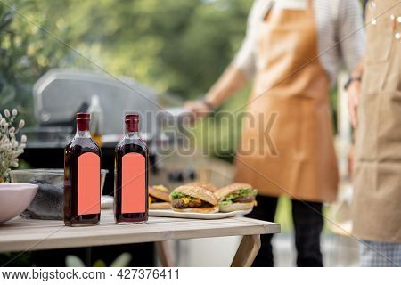 Bottles With Liqueur Or Berry Tinctures On A Table With Burgers, People Grilling On A Background, Cl