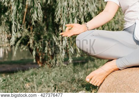 Meditation In Nature. Close-up Of Meditating Yoga Woman Sitting On Stone In Lotus Position Outdoors.