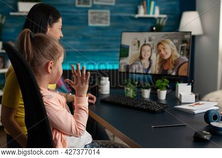 Young Child And Adult Using Video Call With Friends And Family While Being At Home. Mother And Daugh