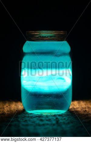 Jar With Blue Liquid On A Dark Background. Light Passes Through The Jar.