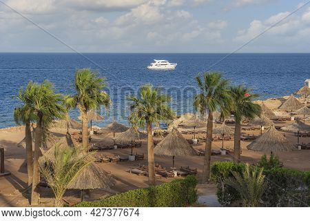 White Boat In The Sea Near The Luxury Sand Beach With Beach Chairs, Straw Umbrellas And Palm Tree In