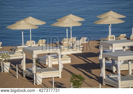 Luxury Sand Beach With Beach Chairs And White Straw Umbrellas In Tropical Resort In Red Sea Coast In