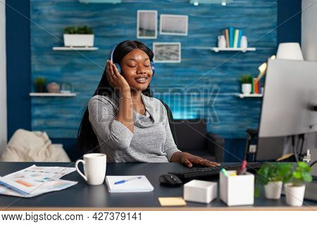 African American Student Wearing Headphones Listening Happy Music Sitting At Desk In Living Room. Wo